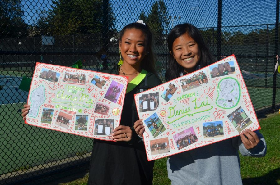 Anna Ma and Denise Lai hold up posters celebrating their last season as seniors.